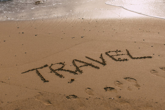 beach with travel lettering on sand near sea