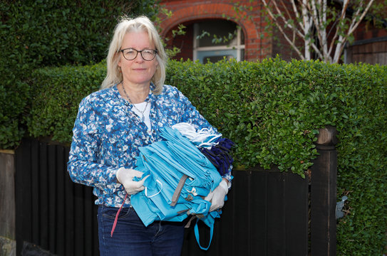Hilary Reed an interior designer by profession hands out supplies to her neighbours in London
