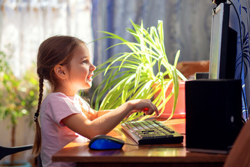 Girl schoolgirl is sitting at home at a computer desk and is engaged on a desktop computer. Home...
