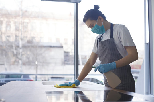 Young woman in mask and gloves making disinfection of kitchen
