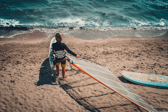 Rear View Of Person With Windsurf Board At Beach