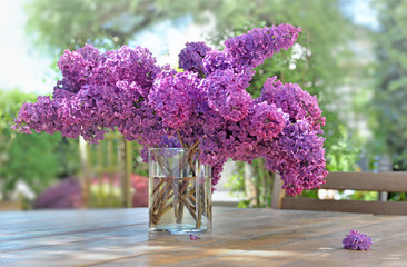 Photo sur Aluminium Lilac beautiful bouquet of purple lilac on a wooden table in garden