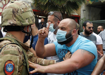 A Lebanese demonstrator gestures to a Lebanese soldier, during a protest against the collapsing Lebanese pound currency and the price hikes, in Zouk, north of Beirut