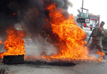 Lebanese soldier reacts near a burning tire during a protest against the collapsing Lebanese pound currency and the price hikes, in Zouk, north of Beirut