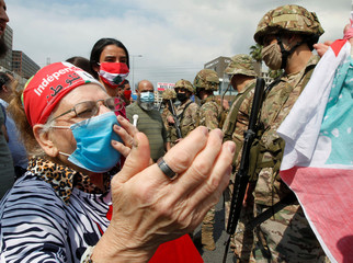An elderly woman wearing a face mask gestures during a protest against the collapsing Lebanese pound currency and the price hikes, in Zouk, north of Beirut