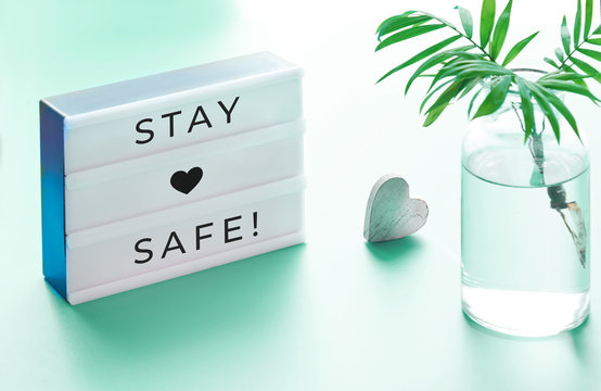 """Lightbox with text """"Stay safe"""", glass bottle with palm leaf and wooden heart. Wishing well to friends and family during quarantine and social distancing due to Covid-19 pneumonia in many countries"""
