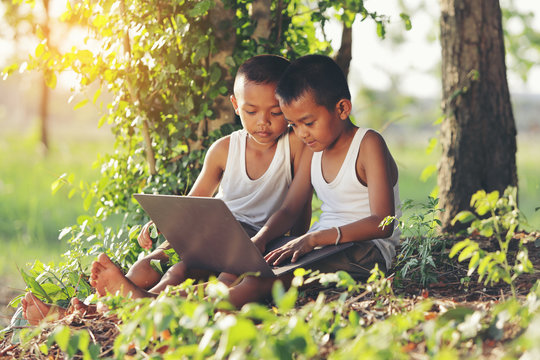 Two boy in the countryside is studying via wireless internet.