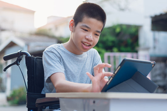 Disabled child on wheelchair happy time to use a tablet in the house, Study and Work at home for safety from covid 19, Life in the education age of special need kid, Happy disability boy concept.
