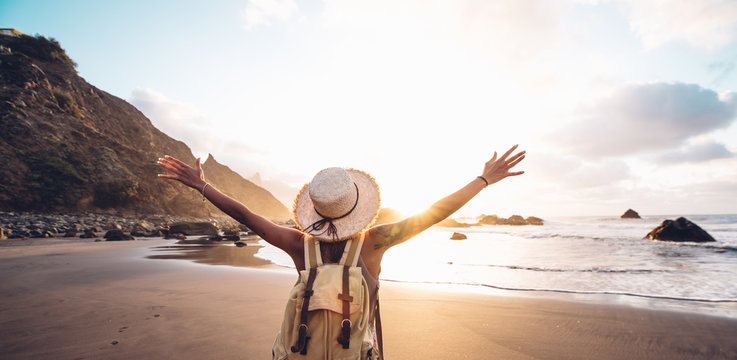 Happy woman with arms up enjoy freedom at the beach at sunset. Wellness, success, freedom and travel concept