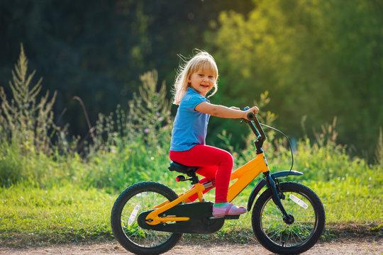 cute happy little girl riding bike in nature