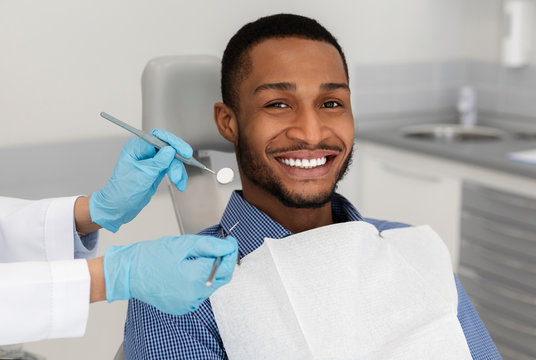 Cheerful african guy in dentist chair, visiting modern clinic