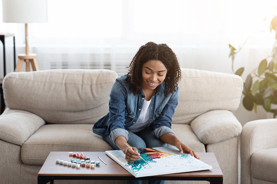 Young black woman drawing picture by numbers with on canvas at home