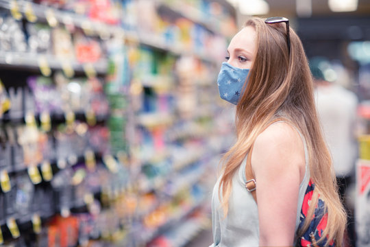A young woman in a department grocery store wearing a face mask. People wearing cloth masks to protect themselves from covid-19 pandemic.