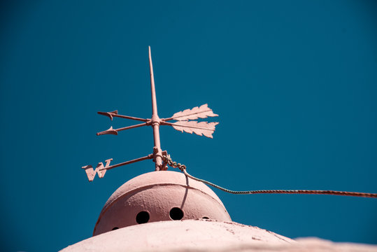 Low Angle View Of Old Weather Vane Against Clear Blue Sky