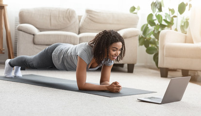 Fit black woman training at home, watching online tutorial on laptop