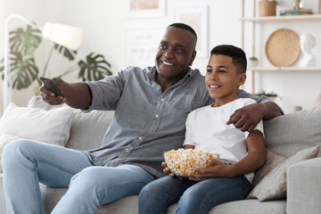 Happy African American Grandfather Watching TV With Grandson At Home Together