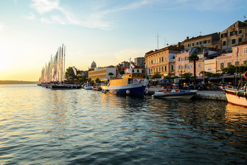 Waterfront promenade of Šibenik in Croatia along the Adriatic Sea, at sunset - Medieval buildings on the hill of this historical town Fototapete