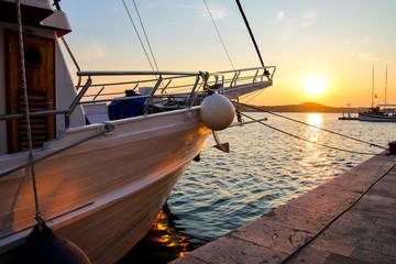 Sailing ships moored in the waterfront marina of Šibenik, Croatia, in the Adriatic Sea, at sunset Fototapete