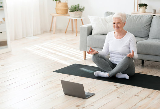 Yoga online. Relaxed senior woman meditating in front of laptop at home