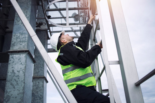 Industrial factory construction worker climbing metal ladder of production plant in sunset.