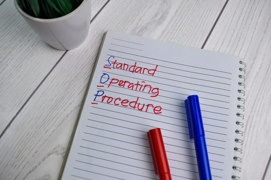 SOP - Standard Operating Procedure write on a book isolated on office desk