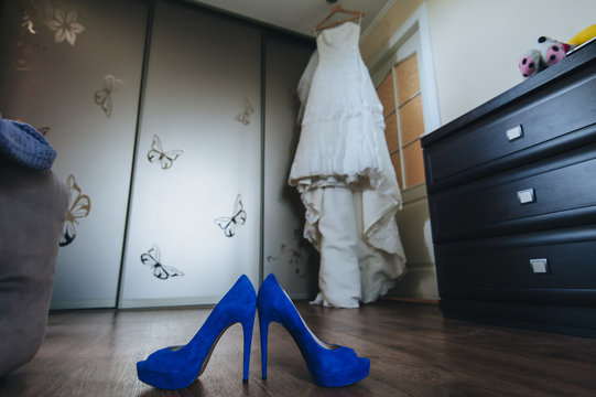 Blue suede bride's shoes stand against the backdrop of a white wedding long dress hanging on a hanger against a wardrobe in a beautiful interior. Photography, concept.