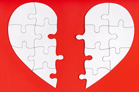 Two matching halves of one heart on red. Care, health, support, love concept. Separation, divorce, broken heart, break up metaphor. Perfect match, reunion. Finding love partner. Jigsaw puzzle
