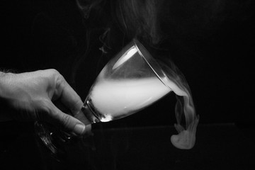 Cropped Image Of Man Holding Glass With Smoke Against Black Background