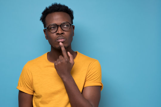 Young african american man, student with finger in mouth in deep thought