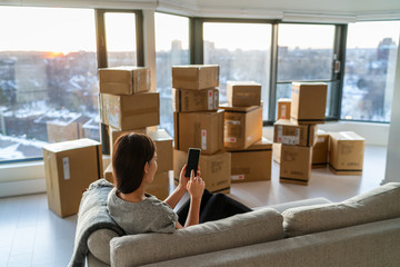 Fototapeta Home move out of apartment moving boxes woman using online movers services on mobile phone app easy pick-up with packages for new home. Asian new homeowner girl happy sitting in sofa. obraz