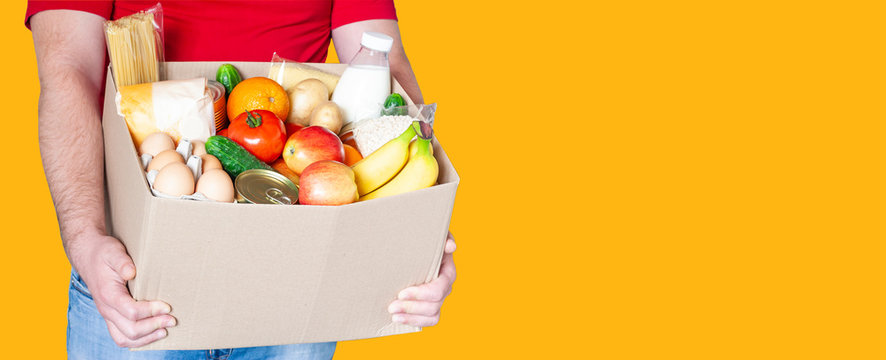 Grocery delivery courier man in red uniform holds cardboard box with fresh vegetables, fruits and other food on orange background. Express food delivery, donation concept.