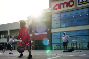 Aiden Miller, 9, foreground, and Greyson Miller, 8, left, (no relation), practice basketball moves in a parking lot in front of an AMC movie theater in Smyrna