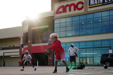 Aiden Miller, 9, foreground, and Greyson Miller, 8, left, (no relation), practice basketball moves in an AMC theater parking lot in Smyrna