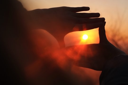Close-up Of Hands Framing The Sun At Sunset