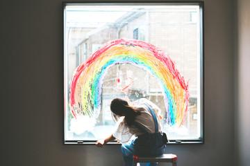 窓に虹を描く少女