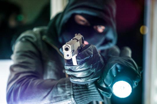 Close-up Of Thief Holding Gun