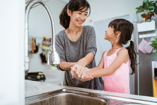 mother and daughter wash their hand together in the kitchen sink