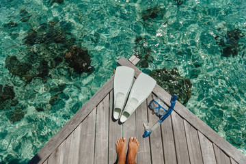 Fototapeta Beach vacation snorkel girl snorkeling with mask and fins. Equipment for snorkeling. Woman legs on wooden pier with snorkeling equipment obraz