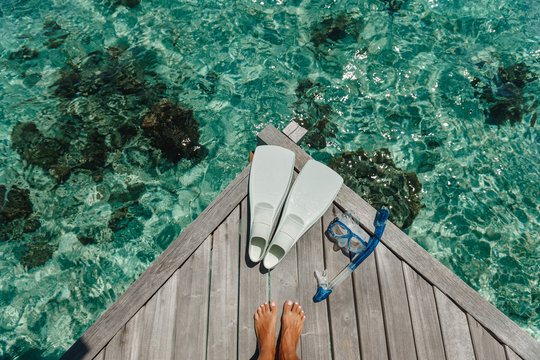 Beach vacation snorkel girl snorkeling with mask and fins. Equipment for snorkeling. Woman legs on wooden pier with snorkeling equipment