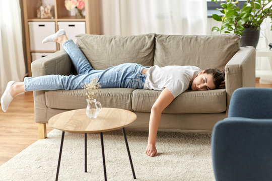 people, boredom and depression concept - bored or lazy young woman lying on sofa at home