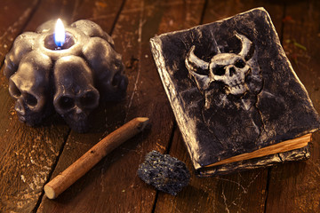 Magic book with devil face and black candle on witch table.