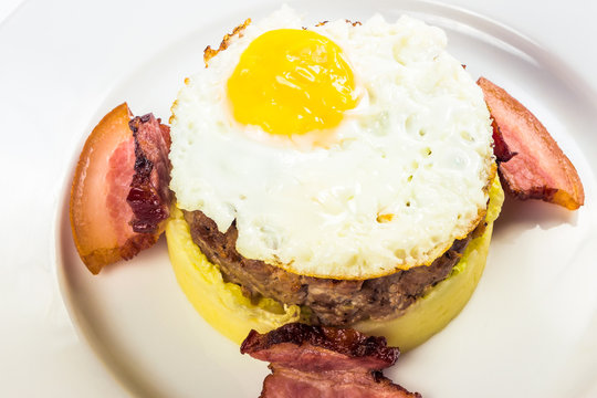 healthy homemade breakfast. fried egg and meat patty on top of smashed potato, decorated with bacon. food isolated on the white background