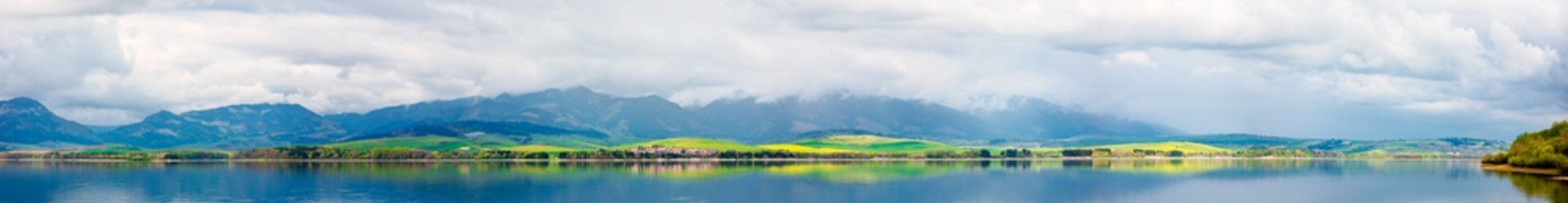 panorama of lake in mountains. cloudy day in springtime. beautiful scenery of high tatra mountains in dappled light. gorgeous landscape of liptovska mara, slovakia