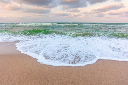 golden cloudy sunset above the green sea waters. waves crashing the sandy beach. clear horizon. changing windy weather