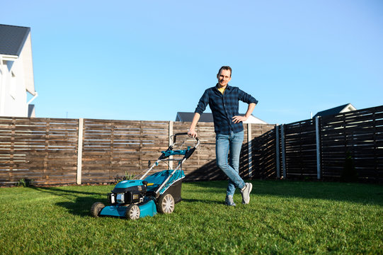 Gardening in the backyard. Young man in a plaid shirt with a push lawn mower on the green grass