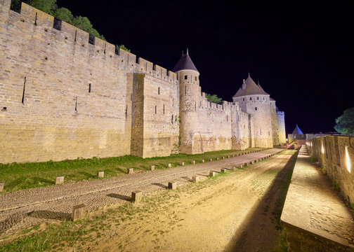 Night view of the ramparts that lead to the main gate of the fortified citadel in the old town of the city of Carcassonne (Cite de Carcassonne), UNESCO world heritage site, Aude department, France