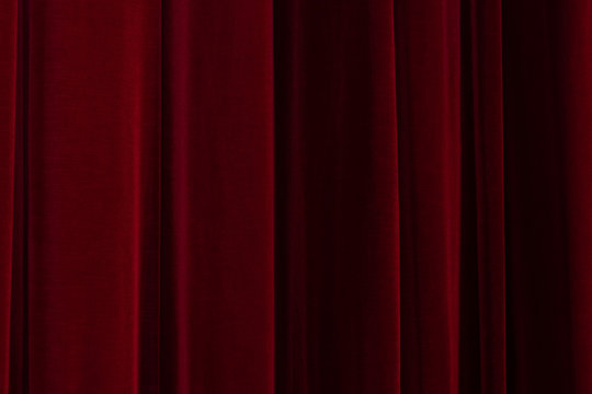 Theatrical dark red velvet curtain. Texture background for design.