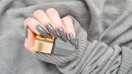 Female hand with long nails dark gray manicure and a bottle of nail polish