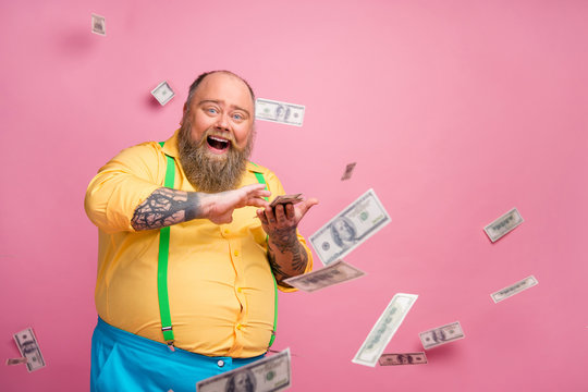 Portrait of his he nice cheerful cheery glad bearded guy throwing interest deposit investment winning cashback having fun currency flying isolated over pink pastel color background