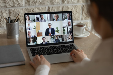Rear close up view of diverse businesspeople talk on webcam conference conversation brainstorming online, employees colleagues speak on video call on laptop, engaged in internet meeting or briefing